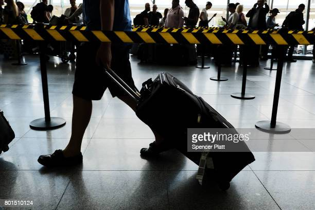 People arrive at John F. Kennedy international airport following an announcment by the Supreme Court that it will take President Donald Trump's...