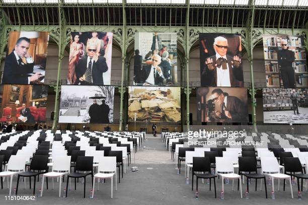 "People arrive at the Grand Palais, decorated with photographs picturing late German fashion designer Karl Lagerfeld, at the start of the ""Karl For..."