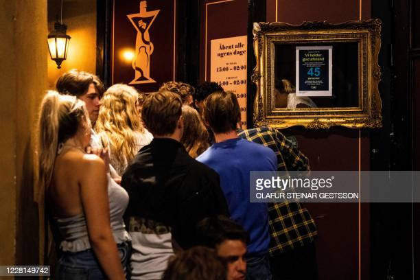 People arrive before 11pm to Ibiza Beach Bar, in Copenhagen, Denmark, on August 21, 2020 as the government demanded that bars keep their doors closed...