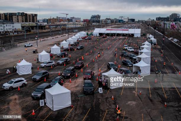 People arrive for Covid-19 vaccination at a drive through setup at Coors Field baseball stadium on January 30 in Denver, Colorado. - UCHealth, the...