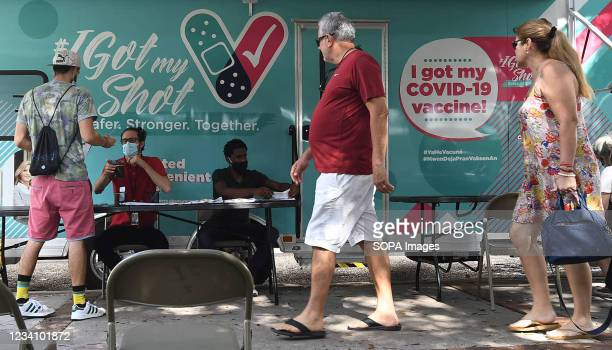 People arrive for shots at a mobile COVID-19 vaccination site. New COVID-19 cases in Florida have doubled in the past week, with most cases...