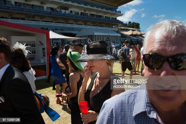 People arrive for the start of the Met horse race at Kenilworth race track on January 27 in Cape Town The Met is one of South Africa's premier horse...