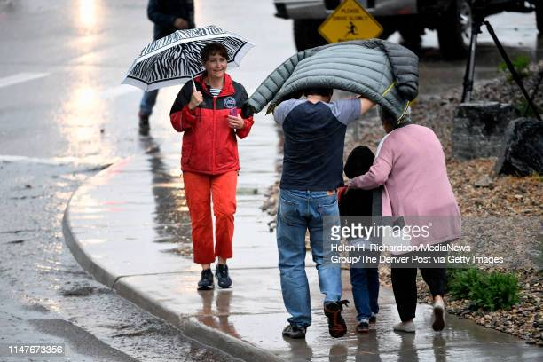 People arrive in the pouring rain at the Highlands Ranch Recreation Center at Northridge to pick up children after a shooting at the STEM school on...