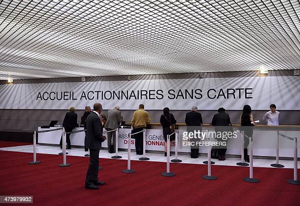 People arrive to attend the French bank Societe Generale's general assembly of shareholders on May 19 2015 in La Défense near Paris AFP PHOTO / ERIC...