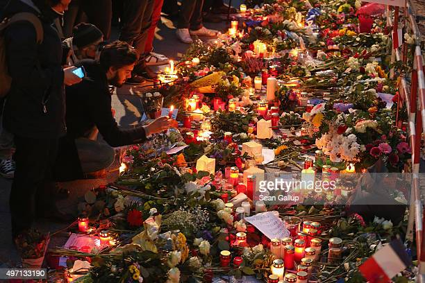People arrive to lay candles and flowers at the gate of the French Embassy following the recent terror attacks in Paris on November 14, 2015 in...