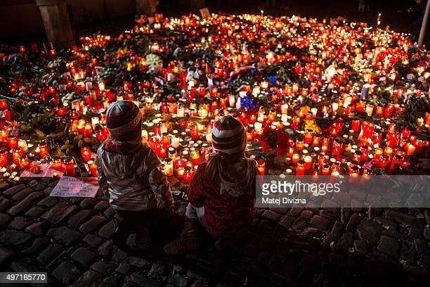 People arrive to lay candles and flowers at the gate of the French Embassy following the recent terror attacks in Paris on November 14 2015 in Prague...