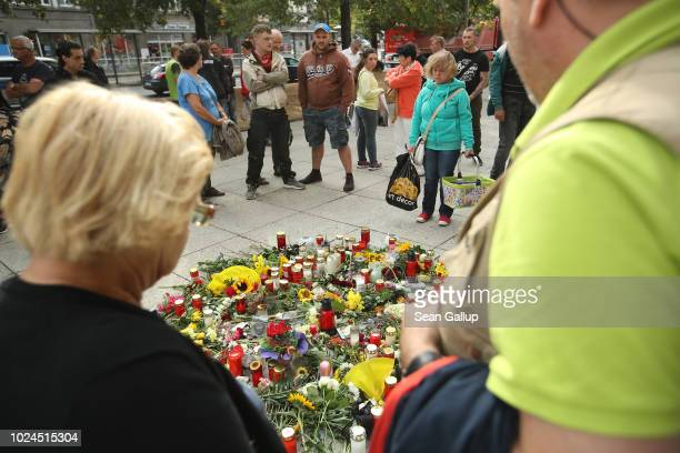 People arrive to lay flowers and candles at the spot where a German man was stabbed and later died of his injuries following an altercation in the...