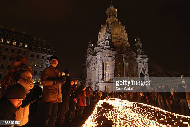 People arrive to light candles next to Frauenkirche cathedral to commemorate the victims of the 1945 Allied firebombing of the city on the 67th...