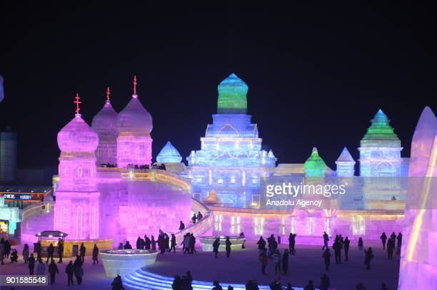 People arrive to visit the illuminated ice castle during the Harbin International Ice and Snow Sculpture Festival at Harbin Sun Island International...