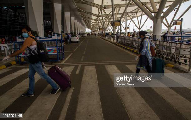 People arrive with their luggage at Terminal 3 at the Indira Gandhi International Airport as the country relaxed its lockdown restriction on May 26...