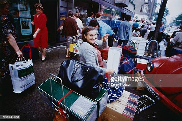 People arriving to exchange their currency on the first day of the reunification of Germany East Berlin 1990 The Deutsche Mark is replacing the East...