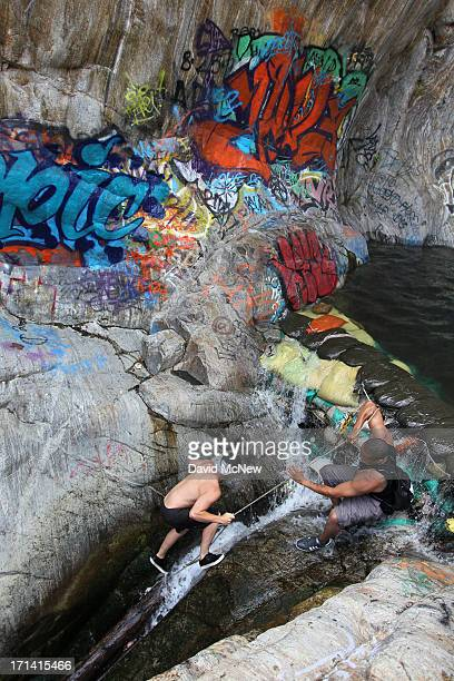 People ascend the creek near graffiticovered rocks at Sapphire Falls in Cucamonga Canyon on June 23 2013 in the Angeles National Forest near Rancho...