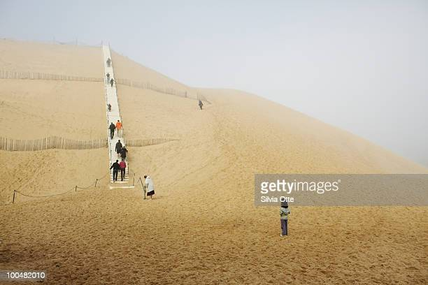 people ascending the stairs to grand dune