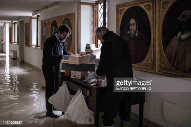 People assess damages in a wing of St Mark's Basilica that houses various objects as key rings rosaries crosses and leaflets after an exceptional...