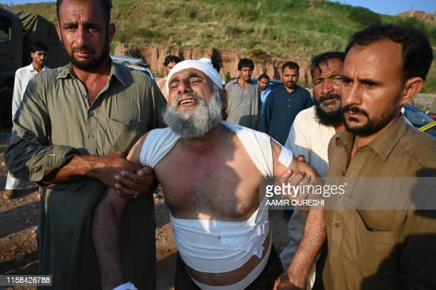 TOPSHOT People assist a man at the scene where a Pakistani Army Aviation Corps aircraft crashed in Rawalpindi on July 30 2019 Seventeen people were...