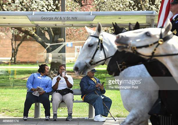 People at a bus stop watch a procession of riders taking part in an event to commemorate the 150th anniversary of President Abraham Lincoln's last...