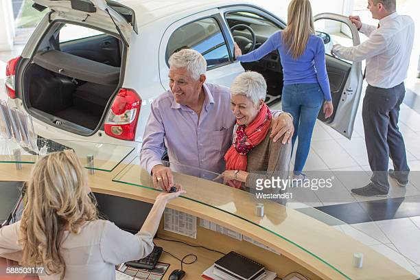 People at a car dealer in showroom