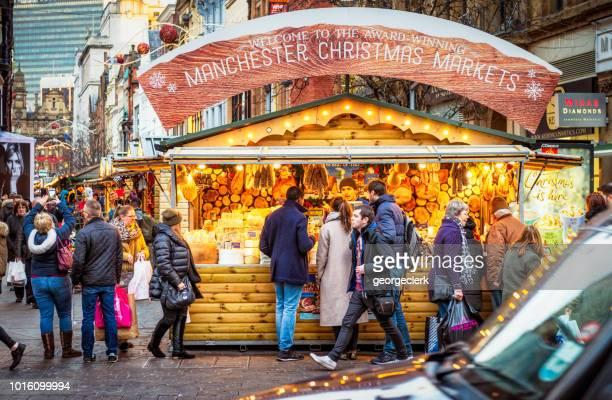 personas en un puesto de navidad en manchester, inglaterra - manchester england fotografías e imágenes de stock