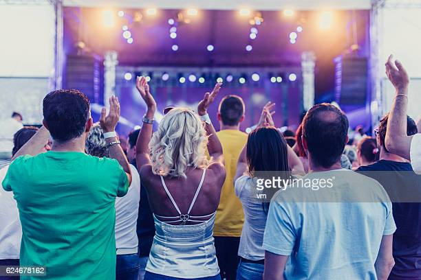 People at a concert listening and clapping