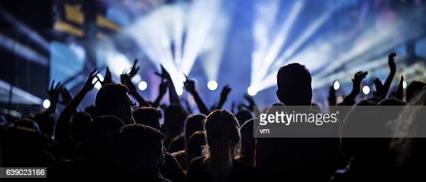 People at a concert with raised hands