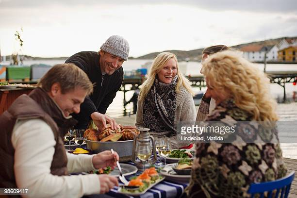People at a dinner party outdoors, Sweden.