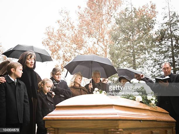 people at a funeral in a cemetery - mourning stock photos and pictures