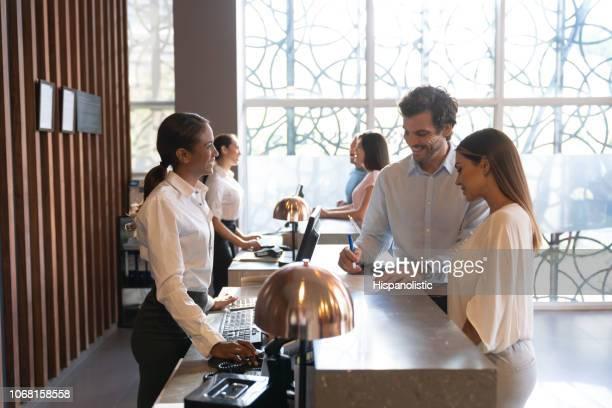 personnes dans un hôtel en profitant de leurs vacances en vérifiant en remplissant un formulaire - hôtel photos et images de collection