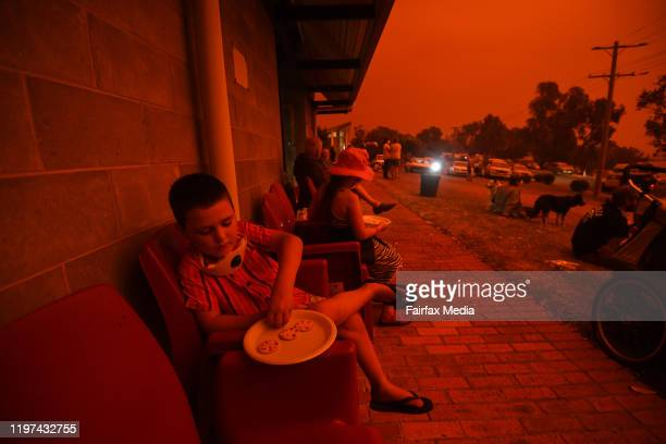 People at a relief centre as day turns to a blood red sky in Mallacoota with the South Westerly change sparking up fire activity in the area on...