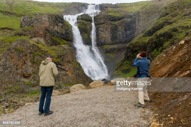 People at a waterfall near Hofteigur in northeastern Iceland