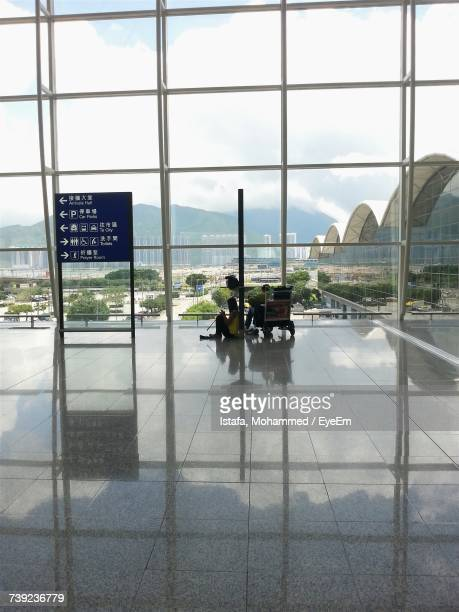 people at airport against sky - hong kong international airport stock photos and pictures