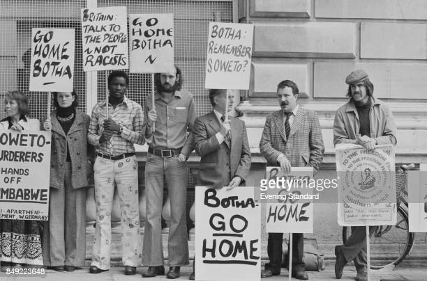 People at an Anti-Apartheid demonstration hold placards and signs against Botha government, 12th August 1977.