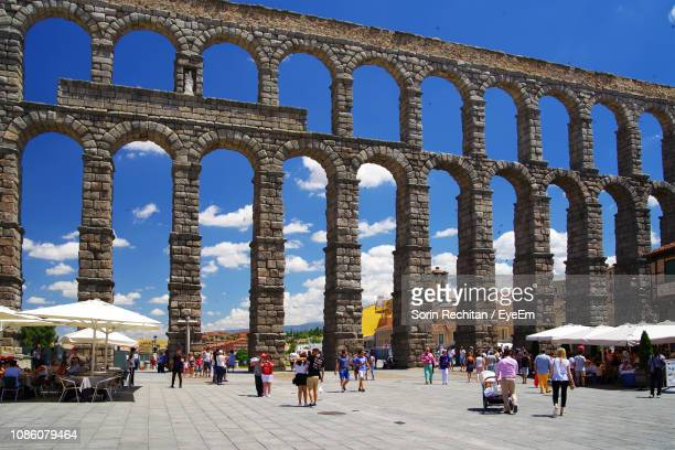 people at aqueduct of segovia in city - segovia stock photos and pictures