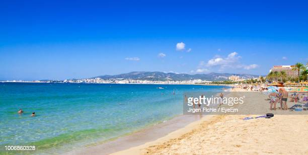 people at beach against blue sky - palma majorca stock pictures, royalty-free photos & images