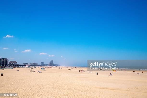 people at beach against blue sky - flanders belgium stock pictures, royalty-free photos & images