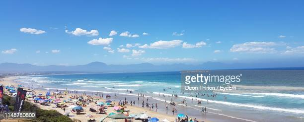 people at beach against blue sky - mossel bay stock pictures, royalty-free photos & images