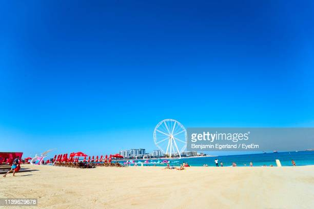 people at beach against clear blue sky during summer - dubai strand stock-fotos und bilder