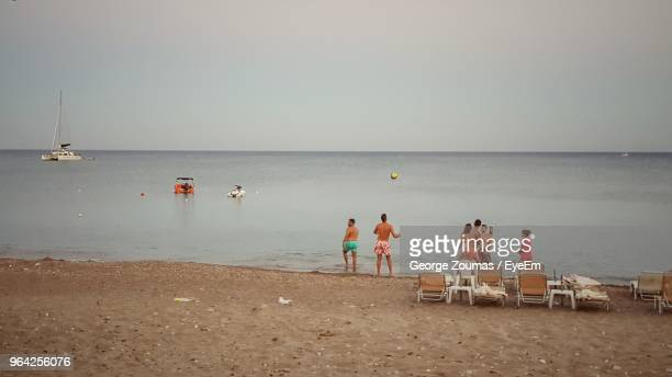 people at beach against clear sky - medium group of people stock pictures, royalty-free photos & images