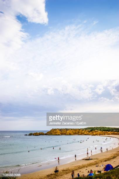 people at beach against cloudy sky - torquay,_victoria stock pictures, royalty-free photos & images