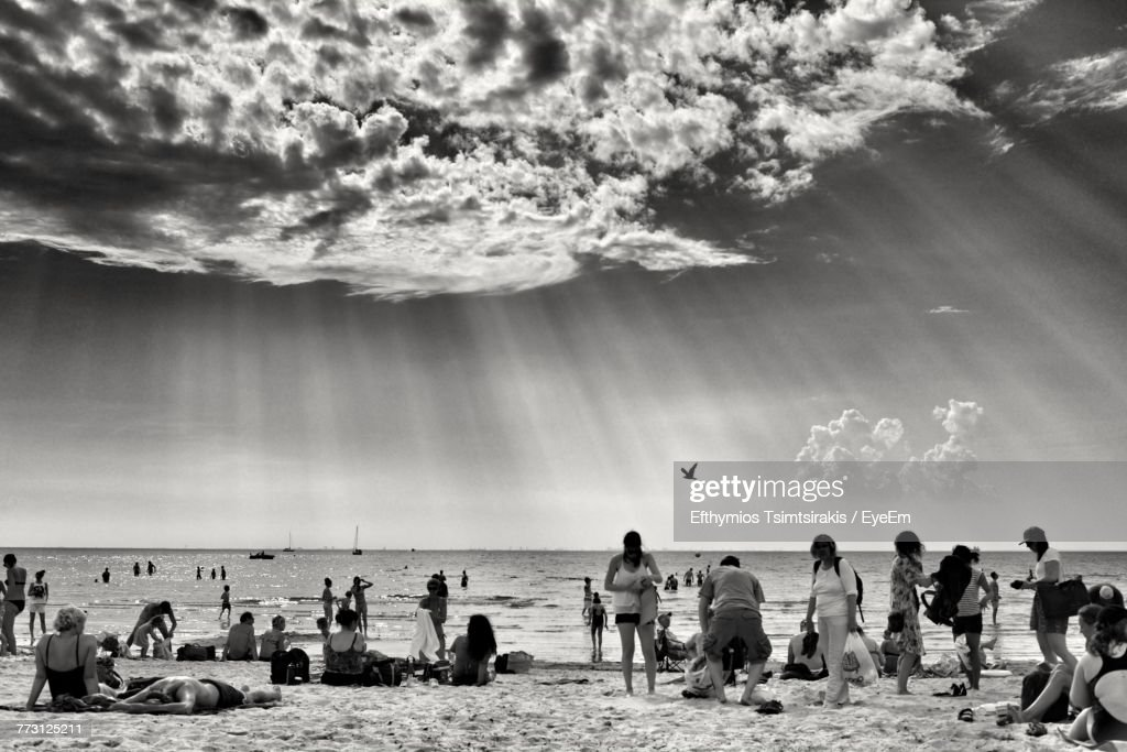 People At Beach Against Cloudy Sky : Photo