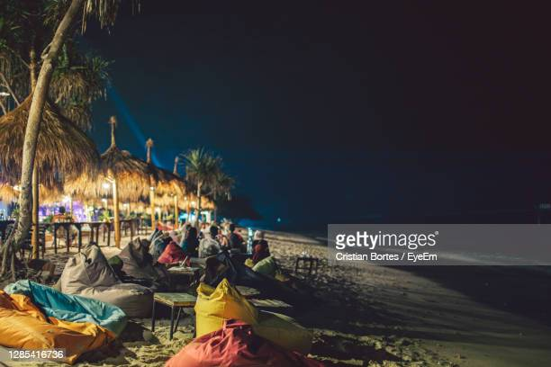 people at beach against sky at night - bortes stock pictures, royalty-free photos & images