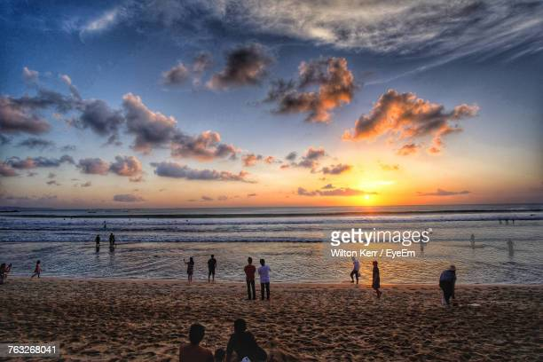 People At Beach Against Sky During Sunset