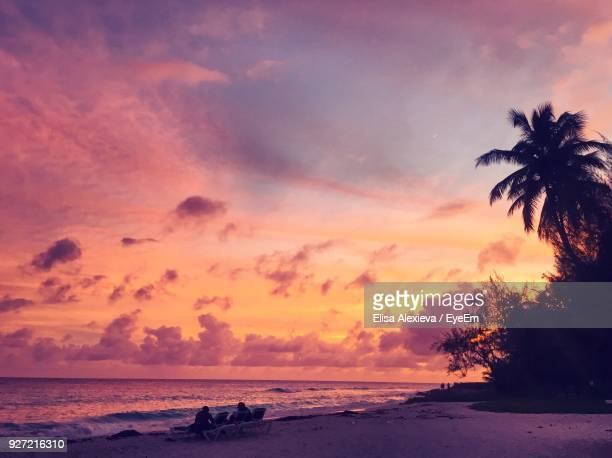 people at beach against sky during sunset - bridgetown barbados stock photos and pictures