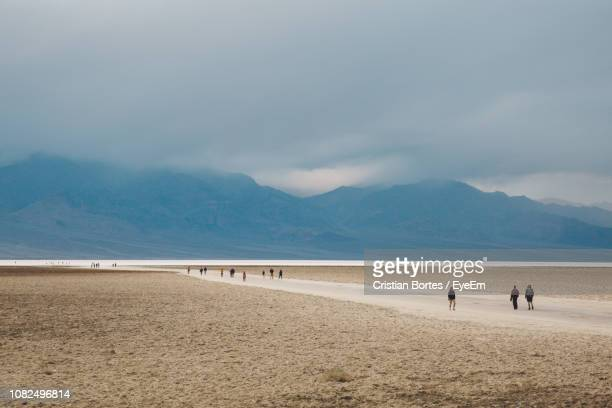 people at beach against sky - bortes stock pictures, royalty-free photos & images