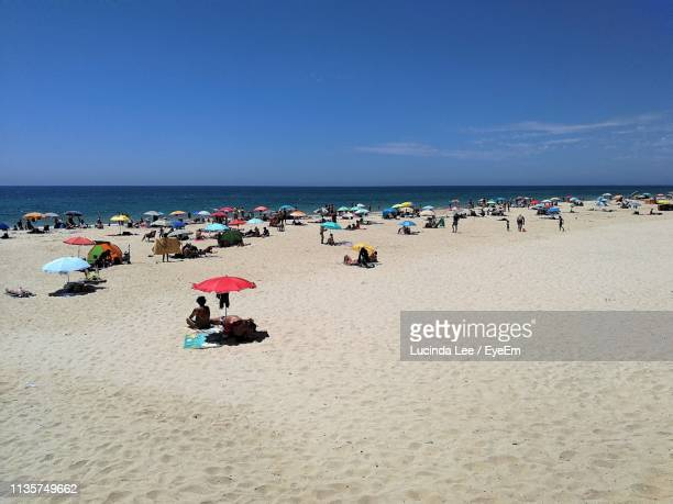 people at beach against sky - lucinda lee stock photos and pictures