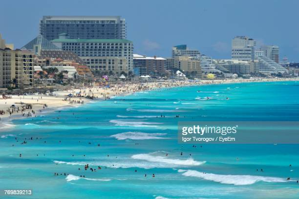 people at beach against sky - cancun stock photos and pictures