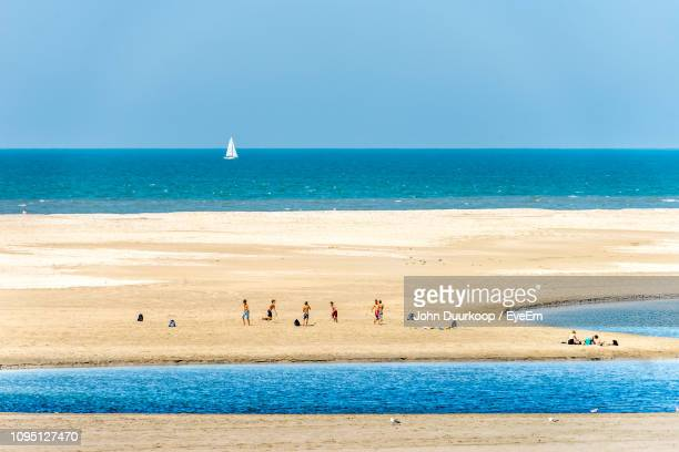 people at beach during sunny day - la haye photos et images de collection