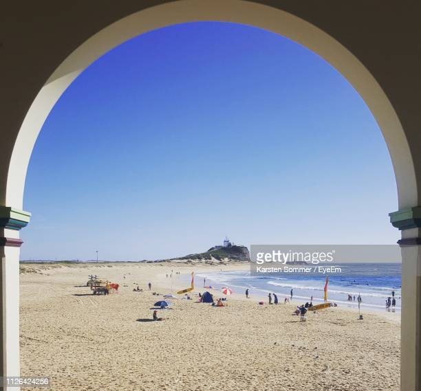 people at beach seen through archway against clear blue sky - 豪州 ニューカッスル ストックフォトと画像