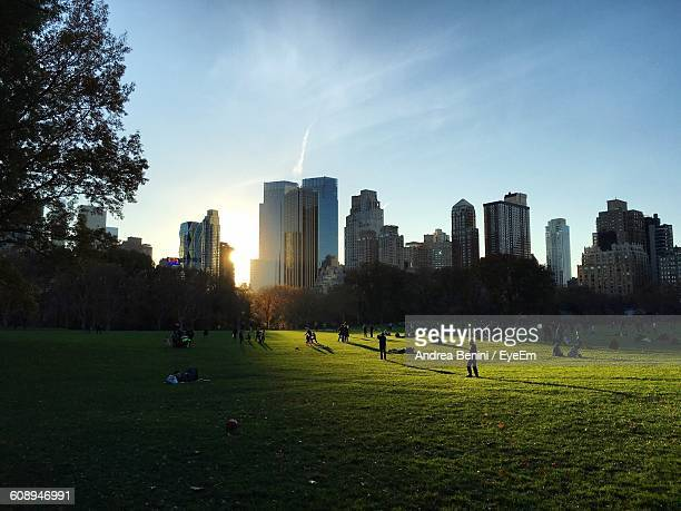 people at central park with city buildings seen in background - central park fotografías e imágenes de stock