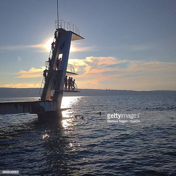 People At Diving Platform In Sea Against Sky During Sunset