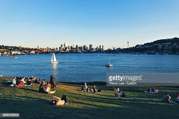 people at gas works park by lake union against blue sky - seattle stock pictures, royalty-free photos & images
